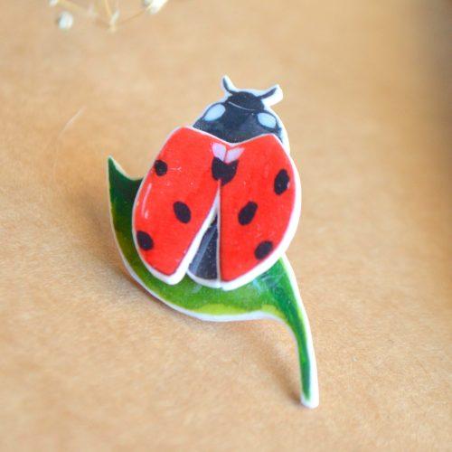 Pin mariquita roja con hoja
